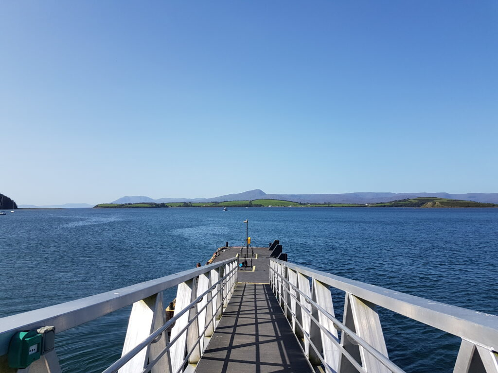 Colour photo taken from the top of a pontoon. The ramp leads down from the foreground to the pontoon, surrounded by calm dark blue sea. There is a low line of green hills on the horizon. The top half of the image is filled with blue sky.