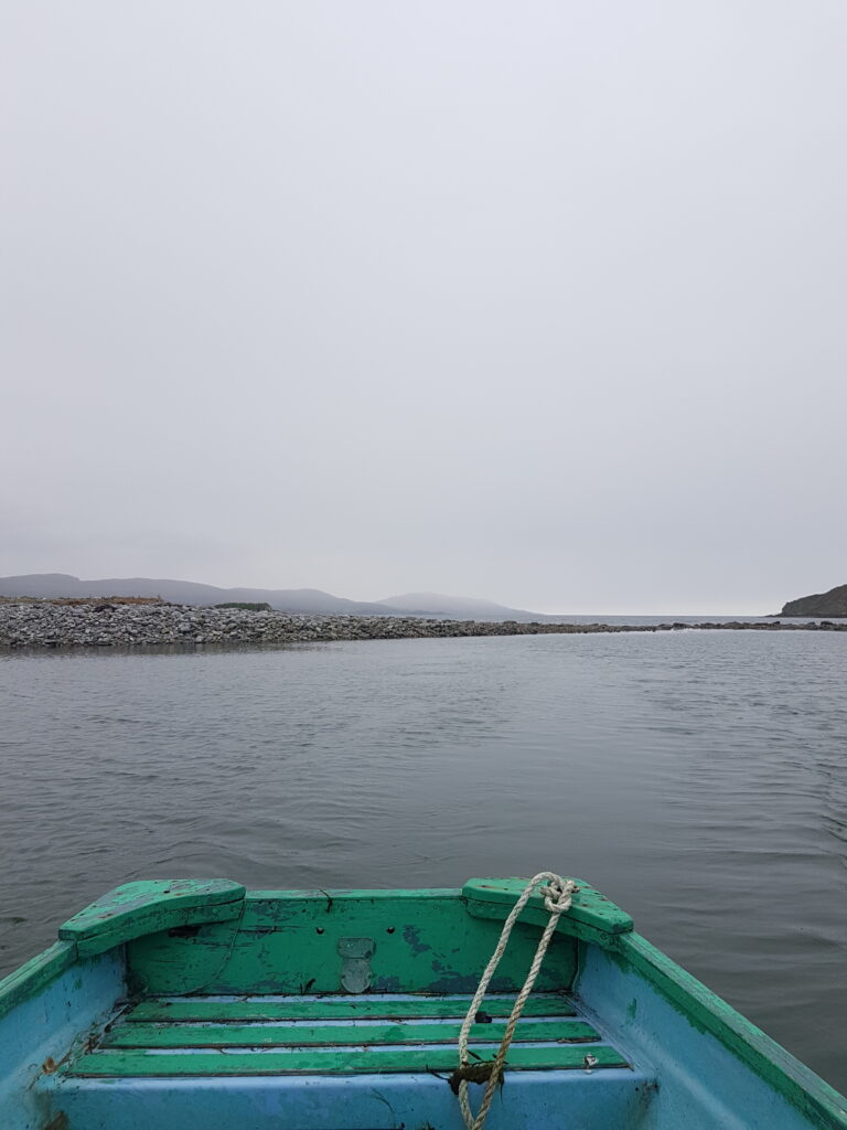 Colour photo taken from a small old green and blue wooden rowing boat, with the back of the boat visible in the immediate foreground. The boat is on a calm dark lake. Distant hills and a misty sky are visible beyond.