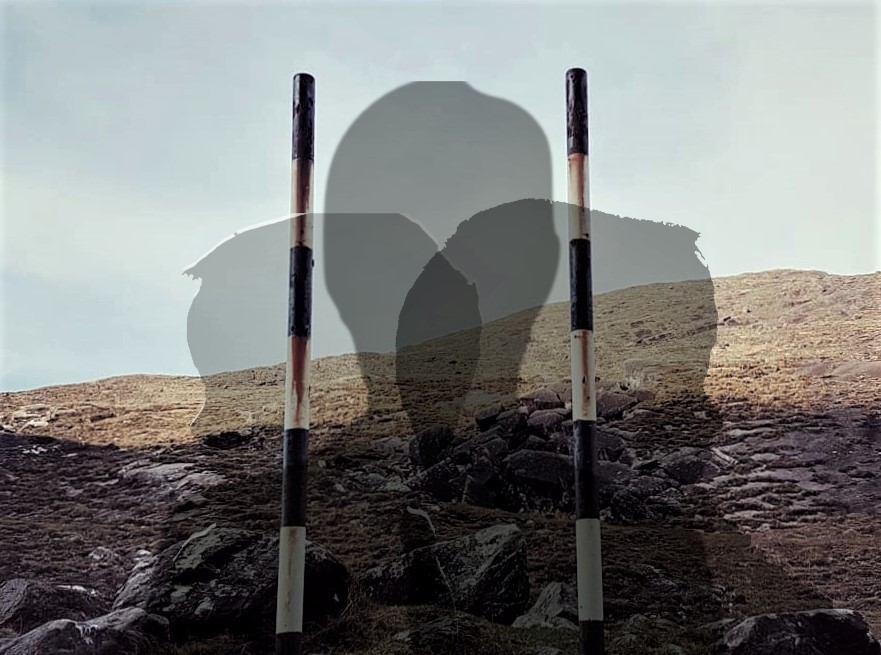 Composite image: the background is a colour photograph of a rocky mountain landscape topped with grey sky. In the center foreground are two old black and white striped signposts about a metre apart: the sign is missing or has been removed. Overlaid on this image are the partly transparent head and shoulder silhouettes of three human figures.